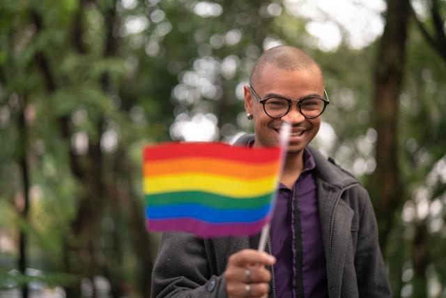 man with lgbt flag