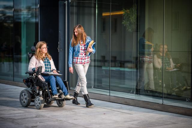 woman in wheelchair strolls with another woman