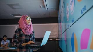 woman wearing hijab looking at whiteboard