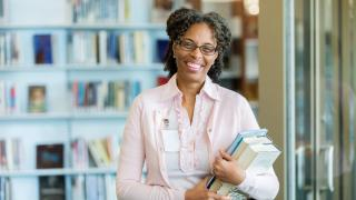 professional woman holding books looking directly at camera