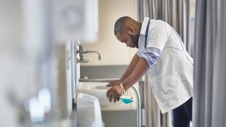 healthcare worker leaning over a sink