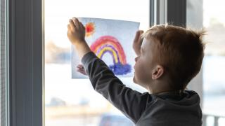 young boy sticking his drawing on home window