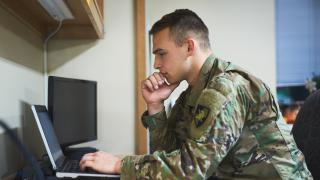 military man looking at laptop
