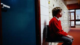 schoolboy sitting on chair in corridor