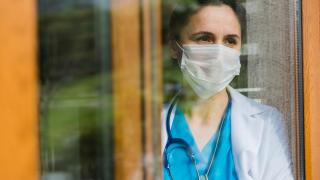 Female doctor looking through window at hospital